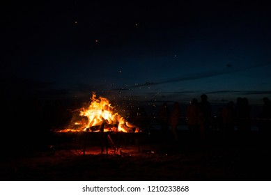 Large burning bonfire with soft glowing flame and sparkles flying all around. Romantic summer evening, people relaxing and enjoying calmness at the festival on seaside. Stage, singers in background