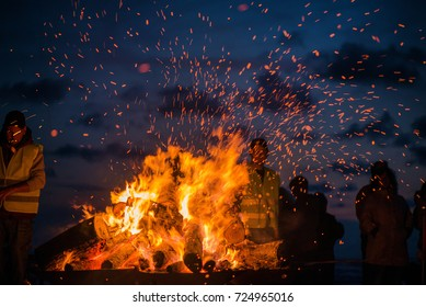 Large burning bonfire with soft glowing flame and sparkles flying all around. Romantic summer evening, people relaxing and enjoying calmness at the seaside during the Night of ancient lights