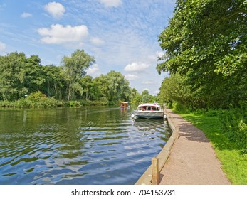 A large cabin cruiser moored on the banks of the River Bure, on the Norfolk Broads near Wroxham, while a second boat travels upstream.