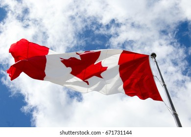 A large Canadian flag flies against a partly cloudy sky.