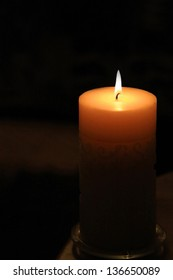 Large candle with flame - candlelight, lit in darkness, religious icon, peace, hope or Christmas or Christian / religious symbol.