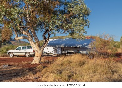 Large caravan and four wheel drive vehicle camped next to a white trunk Snappy Gum tree in the Karijini National Park, Australia in the late afternoon.