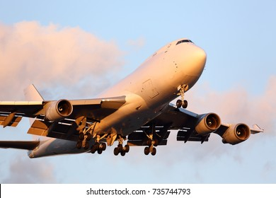 Large cargo aircraft approaching the airport right before sunset