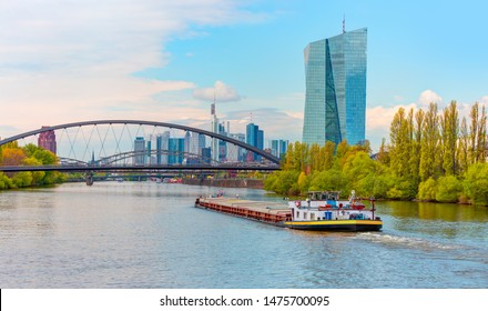 Large Cargo barge moving along the Main River with in the background beautiful view of Frankfurt am Main skyline - Frankfurt, Germany