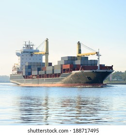 Large cargo container ship leaving port in a bright sunny day. R