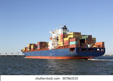 Large cargo container ship passing by a bridge