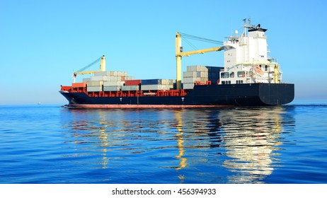 Large cargo container ship sailing in a bright sunny day. Riga, Latvia