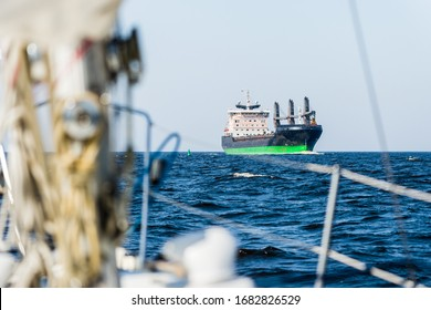 Large cargo crane ship sailing in an open Baltic sea on a clear day. A view from the sailing boat. Waves and water splashes. Latvia