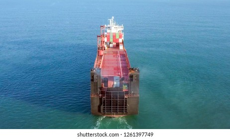 Large Cargo and RoRo (Roll On-Off) ship at sea, loaded with a small amount of shipping containers and two large cranes - Aerial image.