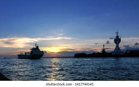 A large cargo ship leaves Kaohsiung Port at sunset