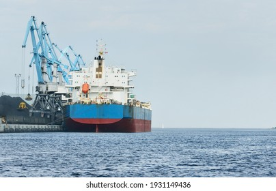 Large cargo ship loading in port terminal, cranes in the background. Freight transportation, nautical vessel, logistics, global communications, worldwide shipping, economy, business, industry