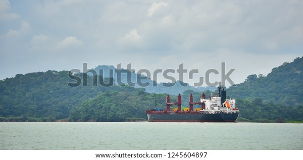 A large cargo ship makes its way through the Panama Canal waterways.  Each side between lift locks is lined with green rain forest jungle.