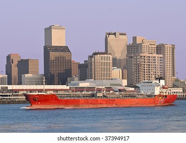A large cargo ship in the Mississippi river sails past the New Orleans skyline