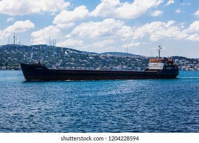 A large cargo ship travels up the Bosporus Strait through Istanbul, Turkey.