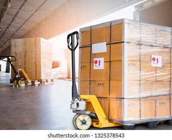 Large cargo shipment pallets. Hand pallet truck with stacked cardboard boxes wrapping plastic on pallet at warehouse dock. warehouse industry freight, logistics and transport.