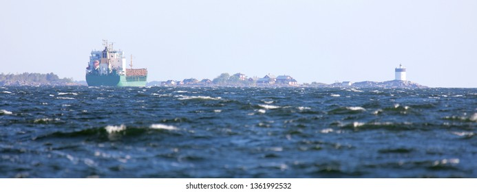 Large carrier ship loaded with timber on the stormy ocean in the swedish archipelago close to the lighthouse Svartklubben