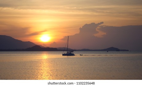 A large catamaran sails on the sea against a beautiful golden sunset. hd