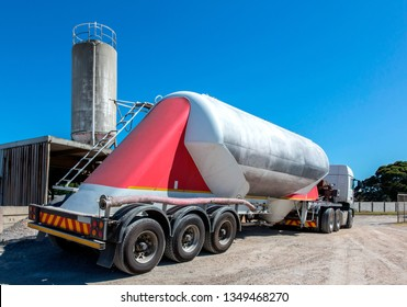 Large cement delivery truck with cement silo in the background