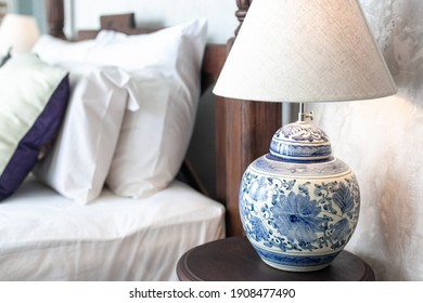 a large ceramic lamp with blue patterns on a white background and a lampshade stands on a wooden bedside table in the bedroom