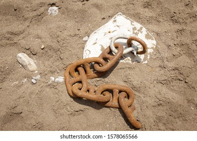 large chain anchor point buried into the beach
