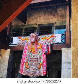 Large Chinese paper costume hangs in front of a shrine.
