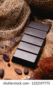 Large chocolate bar on wooden background.