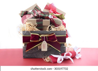 Large Christmas gift hamper with traditional red and green wrapping on red wood table.