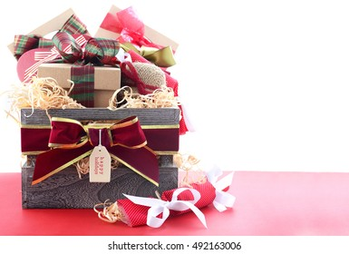 Large Christmas gift hamper with traditional red and green wrapping on red wood table, with copy space.