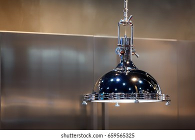 Large Chrome industrial style lamp with shiny stainless steel cabinet in the background.