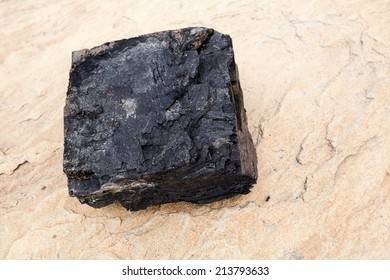 Large chunk of coal on beach. Dimensions around eight inches by eight inches by four inches.