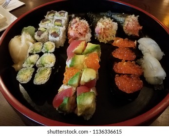 large circular dish with a variety of sushi, rice, and fish eggs