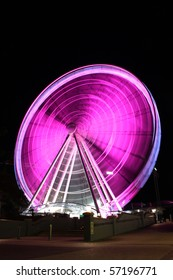 A large city Ferris wheel in pink colors for breast cancer awareness.