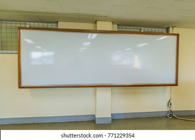 Large classroom white board with wooden frame hanging on the wall with electrical outlet below whiteboard