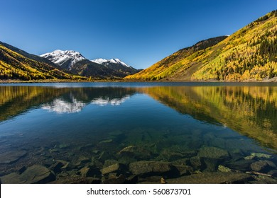 A large, clear mountain lake leads to a golden aspen colored mountain, snow capped peaks and a big beautiful blue sky.