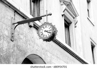 Large clock and wall of a beautiful house against a blue sky.