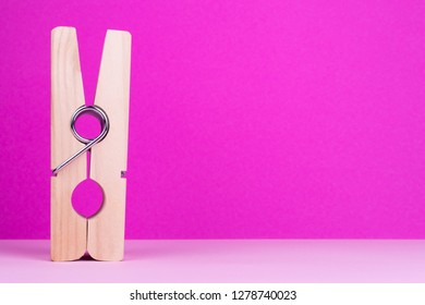Large clothespin on pink background. Decorative clothespin, place for text