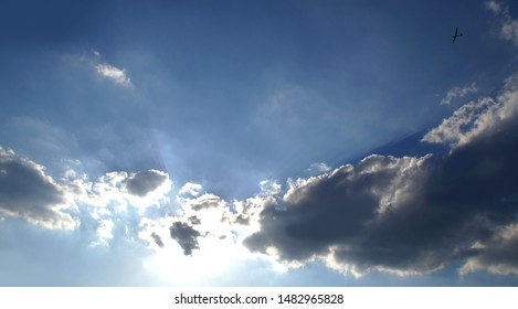 Large clouds hiding the sun with bright rays of light and a tiny glider in the vastness