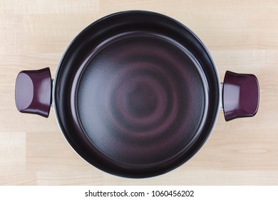 Large coated Stewpot, cooking pot in dark purple ruby color. Cookware with induction technology on wood background, top view