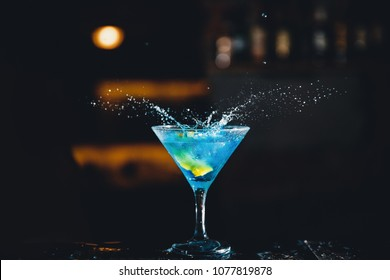 Large cocktail in martini glass with droplets of spray is prepared by barman.