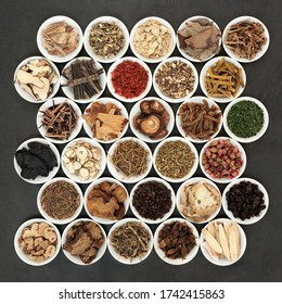 Large collection of Chinese herbs & spices used in herbal medicine in white porcelain bowls on slate background.
