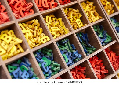 Large collection of colorful plastic alphabet letters stored in a wooden box with square compartments for teaching kids to read and spell, overhead viewful alphabet letters