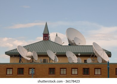 a large collection of communication and broadcast satellite dishes on a rooftop