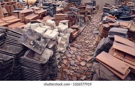 A large collection of different roof tiles, bricks and chimney pots at a salvage yard in the UK.
