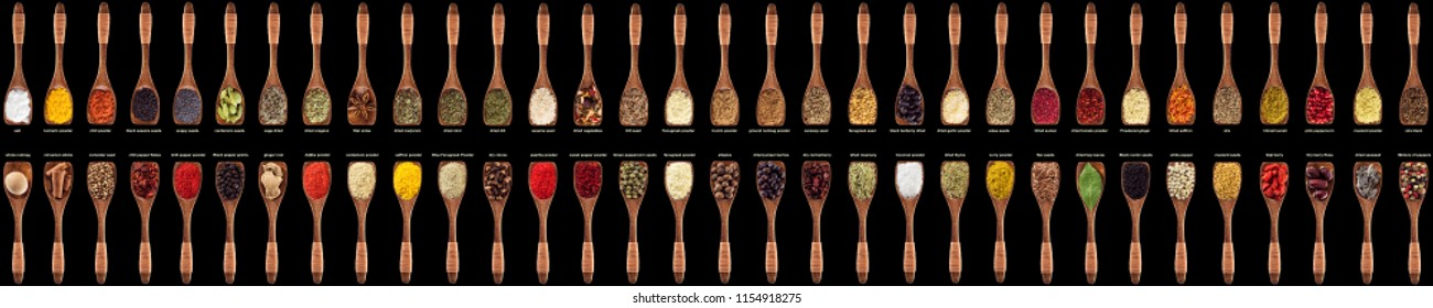 large collection of spices and herbs in wooden spoons. Seasonings for food isolated on a black background, top view.