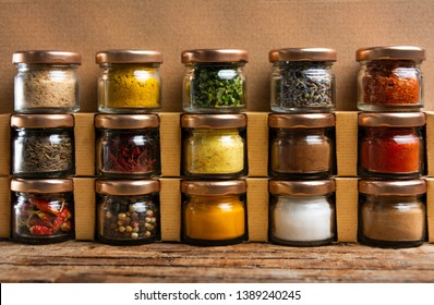 Large collection of spices in small jars on the shelf
