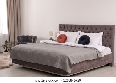 Large comfortable bed near light wall in simple room interior