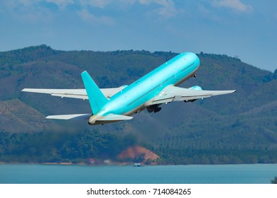 Large Commercial Aircraft Taking Off from Airport with Sea and Mountain Background. Copy Space for Text.