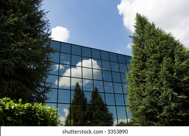 A large commercial office block surrounded by trees that are reflected in the glass.