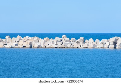 Large concrete cubic blocks for the construction of berths lie in the sea. Breakwater in the bay
