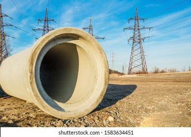 A large concrete pipe for the construction of sewers on the background of high voltage poles